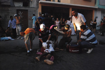A Red Cross paramedic attends to an injured man shot in a drive-by shooting as residents react in Monterrey