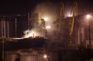 Loading in the bow holds a loose, dusty cargo, night shift, the port of Odessa, Ukraine.