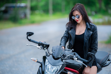 Beautiful woman  wear black leather for driver on the way,Picture of asian lady biker with motorcycle on the road,Thailand peple