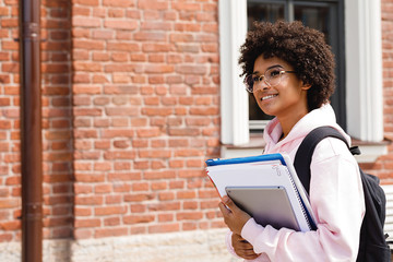 Beautiful student girl with books go to university