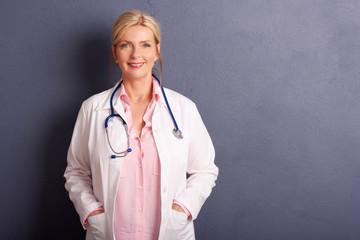 Smiling elderly female doctor portrait. Studio shot.