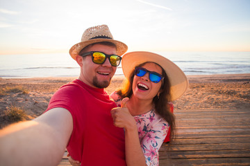 Travel, vacation and holiday concept - Pretty girl and her handsome boyfriend in straw hats make selfie