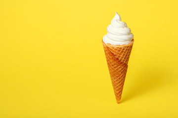 soft vanilla ice cream in waffle cone on yellow background, close up, decoration creative concept