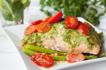 Salmon baked in foil with pesto, tomatoes, asparagus