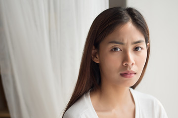 unhappy angry upset asian woman portrait with frustrated, bored, disgusted face; portrait of negative unhappy angry asian woman looking up; young adult asian persian or asian middle east woman model