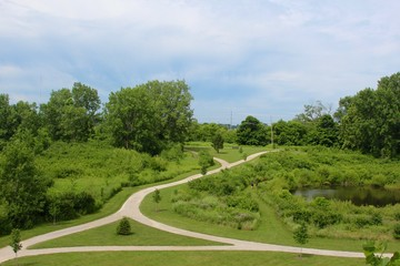The trails and the green grass landscape of the park.