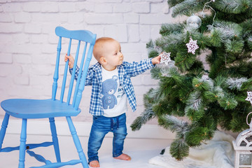 Funny kid boy standing near the Christmas tree and looking at the toys.