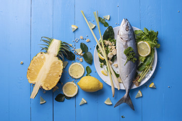 Fish food with ingredient spices on blue table