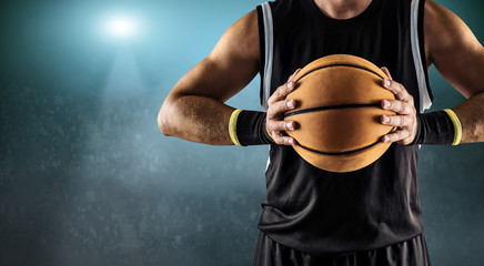 Basketball ball in a male hands, player in black with orange sport ball
