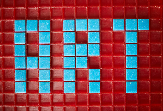 Above view of word ART laid out in blue square tiles over red base