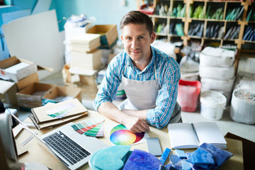 High angle portrait of modern artisan looking at camera and smiling while choosing color palette sitting at table in modern workshop, copy space