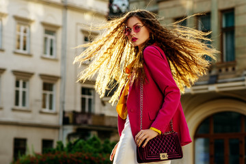 Outdoor fashion portrait of young beautiful woman with very long hair wearing stylish round pink sunglasses, fuchsia color blazer,  holding violet bag, walking in street of european city. Copy space Wall mural