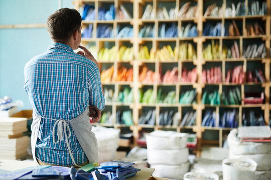 Back view portrait of modern artisan wearing apron choosing materials looking tall shelves in workshop