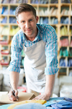 Portrait of modern craftsman wearing apron looking up at camera and smiling while making notes at table un workshop