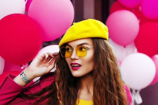 Outdoor close up fashion portrait of young beautiful happy smiling woman wearing trendy yellow sunglasses, beret, posing against pink balloons. Copy, empty space for text