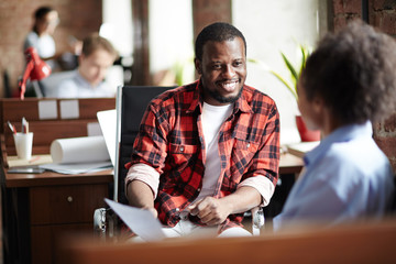 Smiling African businessman in casual clothes conducting the interview with woman at office