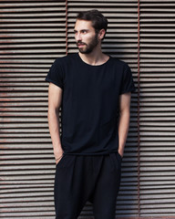 A bearded hipster man in a black T-shirt and pants posing against a metal rusty wall in the afternoon.