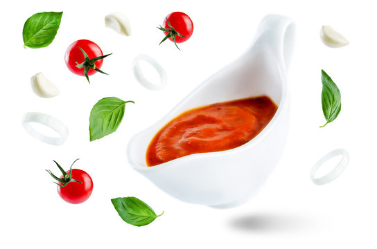 Marinara sauce with flying ingredients to prepare it