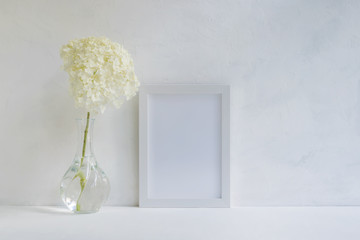 Mockup with a white frame and white flower hydrangea