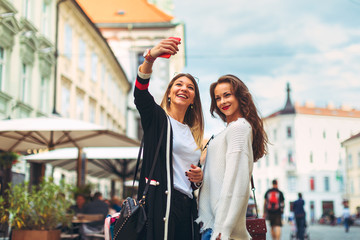 Two young happy women doing selfie in the city