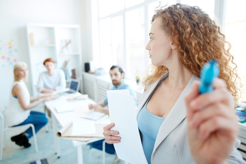 Serious attractive female speaker in jacket holding papers and writing on invisible board while presenting information to employees at training class