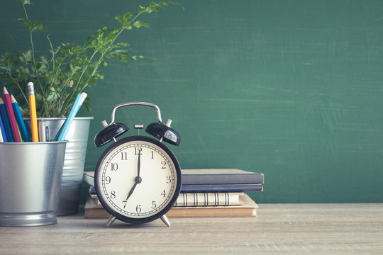 Alarm clock on wooden table on blackboard background in classroom,back to school concept