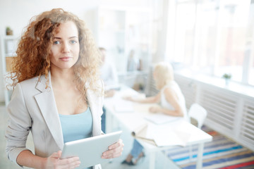Smiling content beautiful curly-haired business specialist in jacket holding modern device and looking at camera while her colleagues discussing project in background