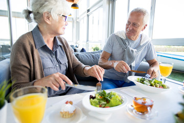Portrait of modern senior couple enjoying lunch and conversation on vacation in resort cafe