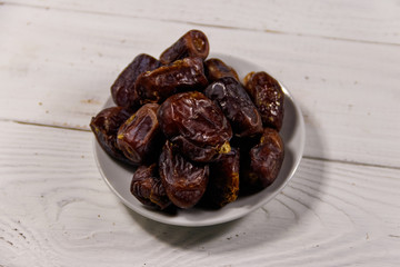 Dried dates fruit on white wooden table