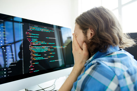 Stressed tired young male computer programmer rubbing face while feeling fatigue and sitting in front of computer with code on monitor