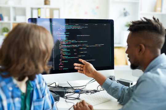 Busy young interracial colleagues analyzing computer code on computer: African man pointing at monitor and asking coworker in office
