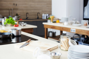 Modern workplace of cooking show: kitchen counter with cutting board, kitchen knife, open glass jar, stack of plates and bowl
