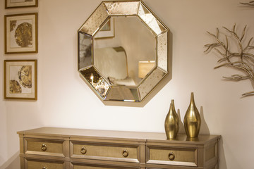 Golden interior, part of the room, a boudoir in gold, a chest of drawers, a mirror, vases, paintings. Modern interior