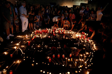 People light candles outside the parliament building to commemorate the victims of a wildfire that left at least 91 dead, in Athens