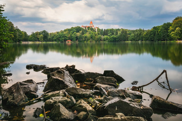 Chateau Konopiste reflected in the water with rock foreground, Central Bohemia, Czech Republic.