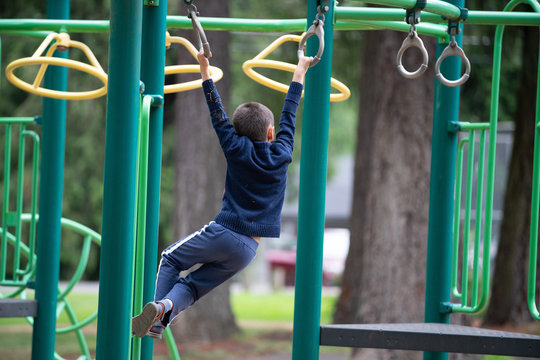 Boy child on monkey bars in the park playground.
