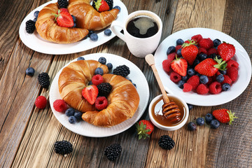 Delicious breakfast with fresh croissants and ripe berries on old marble background.
