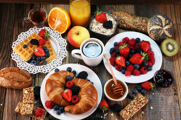 breakfast on table with waffles, croissants, coffe and juice.