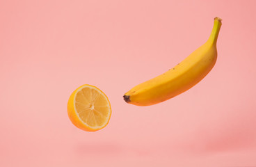 yellow banana and lemon levitate in air on pink background.