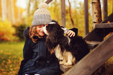 autumn portrait of happy kid girl playing with her spaniel dog in the garden, sitting on wooden stairs and hugs