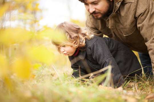 Father and his little daughter together in the forest
