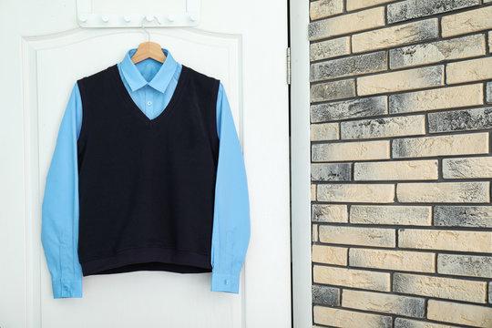 School uniform for boy hanging on white door