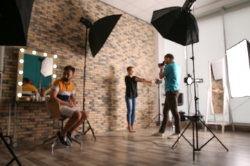 Blurred view of professional team working with model in photo studio