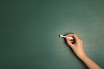 Woman writing with piece of chalk on board
