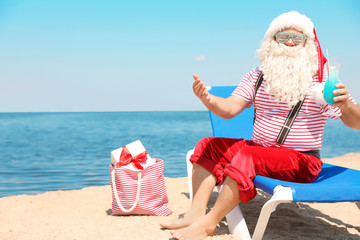 Authentic Santa Claus with cocktail resting on lounge chair at resort
