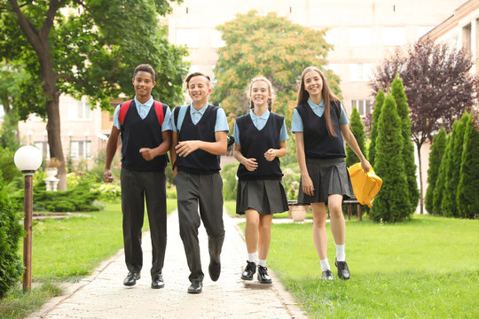 Teenage students in stylish school uniform outdoors