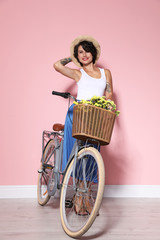 Portrait of beautiful young woman with bicycle near color wall