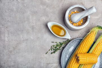 Flat lay composition with gravy boat of corn oil, cobs and kernels on light background