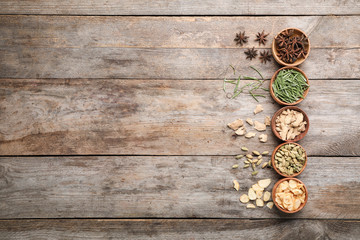 Flat lay composition with different aromatic spices on wooden background