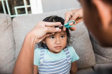 father cutting little girls hair